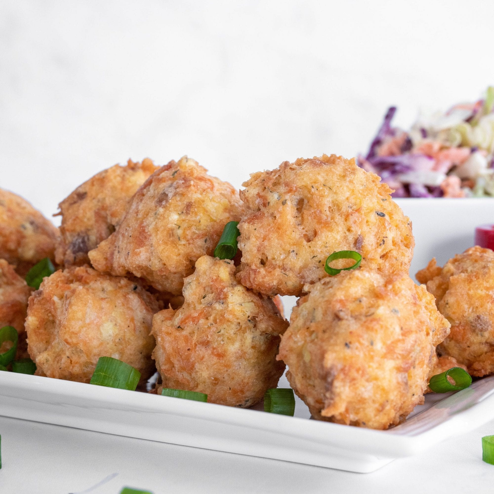 fritters on white tray with coleslaw in the background and tartar sauce. sprinkled with green onions