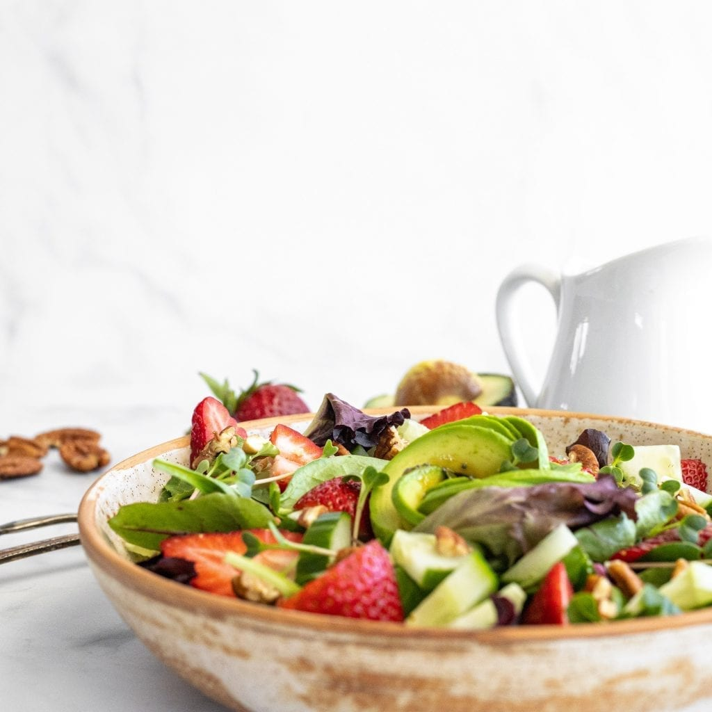 green salad with strawberries in ceramic bowl. white pitcher in the background with balsamic dressing.
