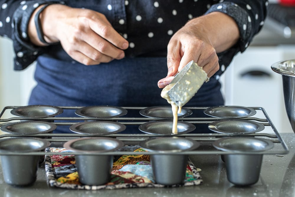 woman pouring whole wheat popover batter into popover pans with a stainless steel measuring cup