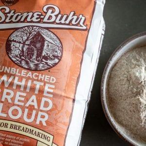 woman adding bread flour to small bowl