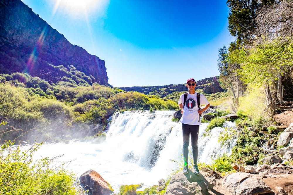 teenage boys standing in front of the falls at Box Canyon State Park in Idaho