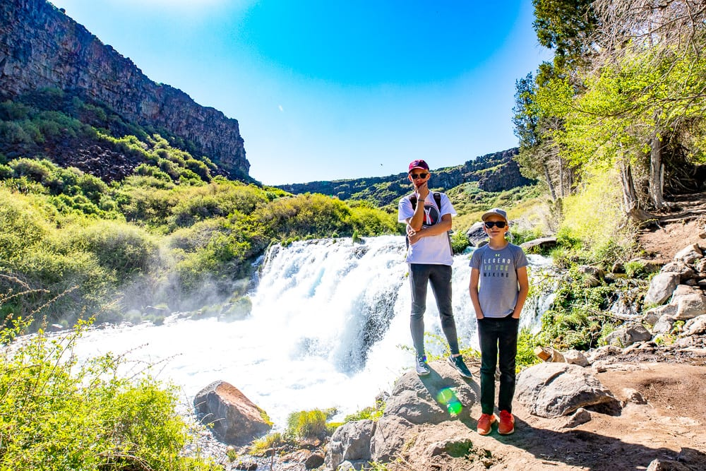 Teenage boy standing in from of the waterfalls at Box Canyon Springs Idaho