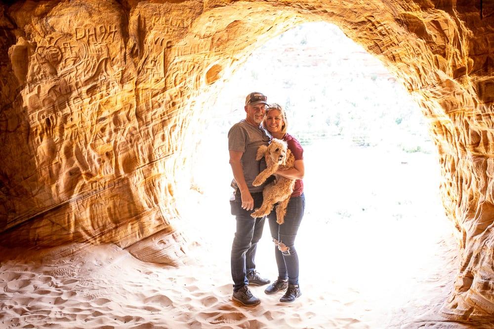 Couple holding cavapoo in moqui caverns