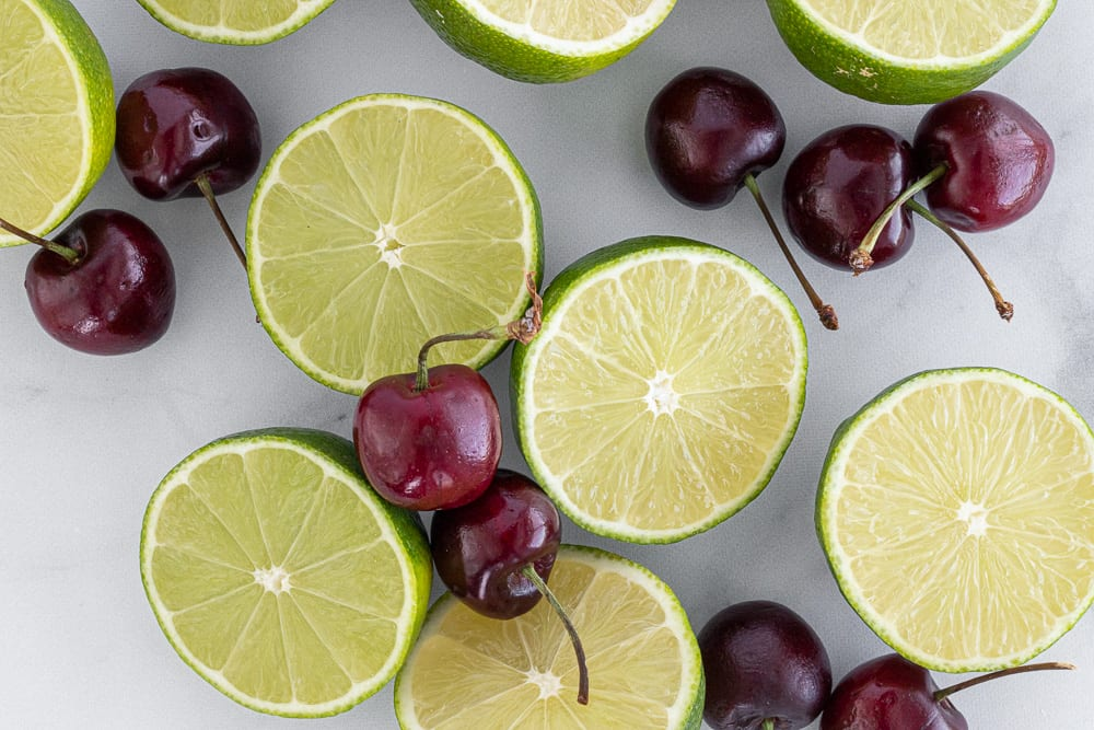 limes and cherries on counter top