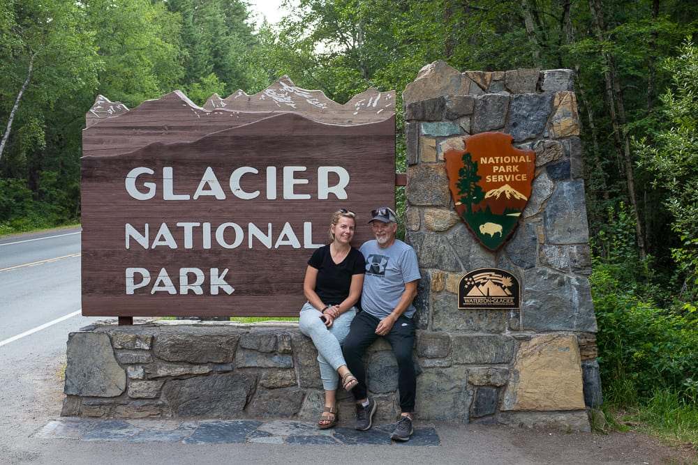 couple in front of the glacier mountain national park sign