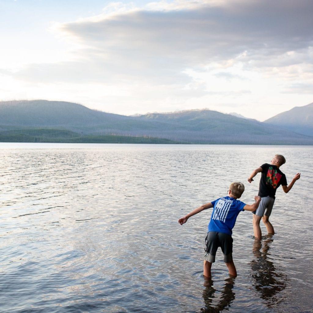 teenage boys skipping rocks on lake McDonald Montana