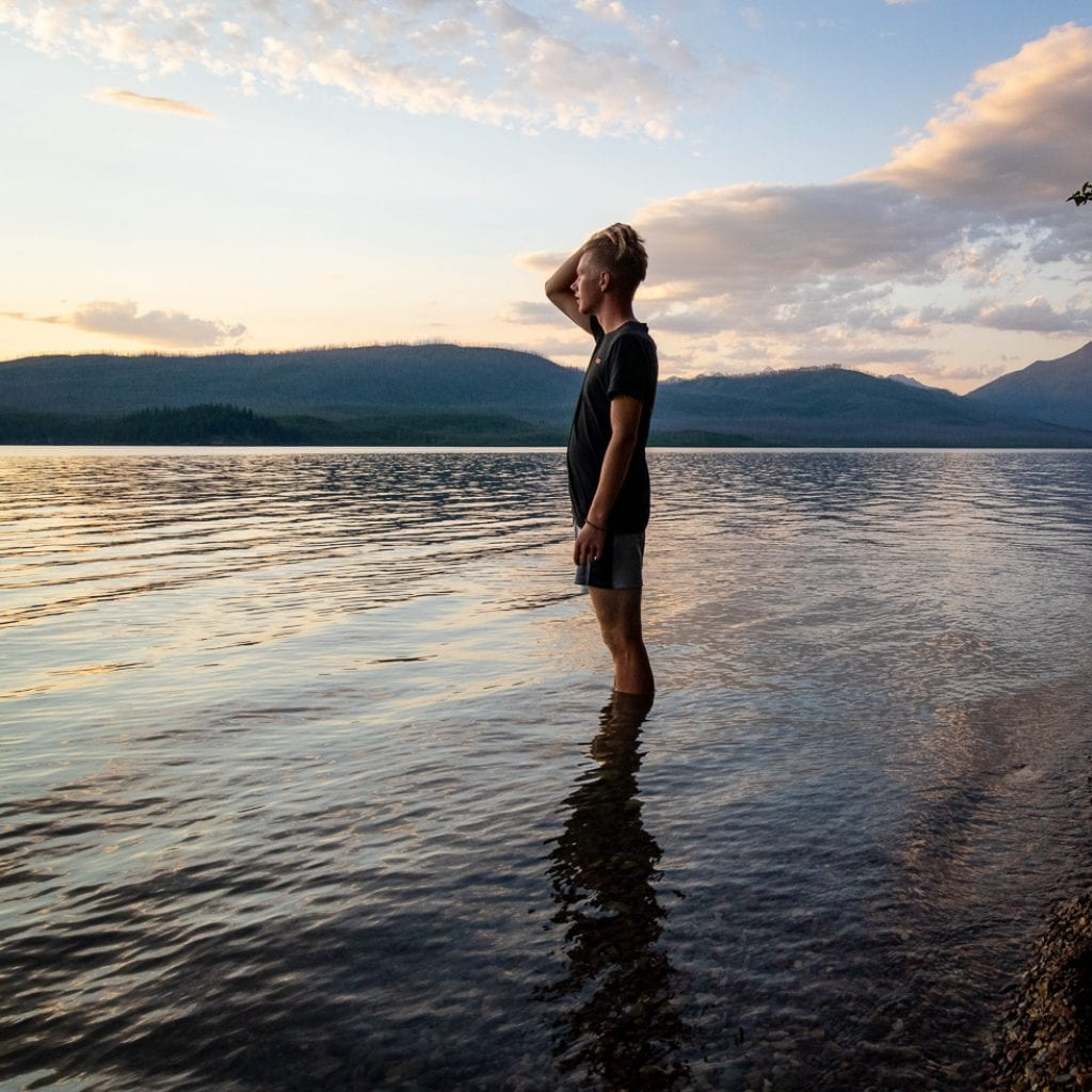 teenage boy running his hand through his hair standing in the water at Lake McDonald