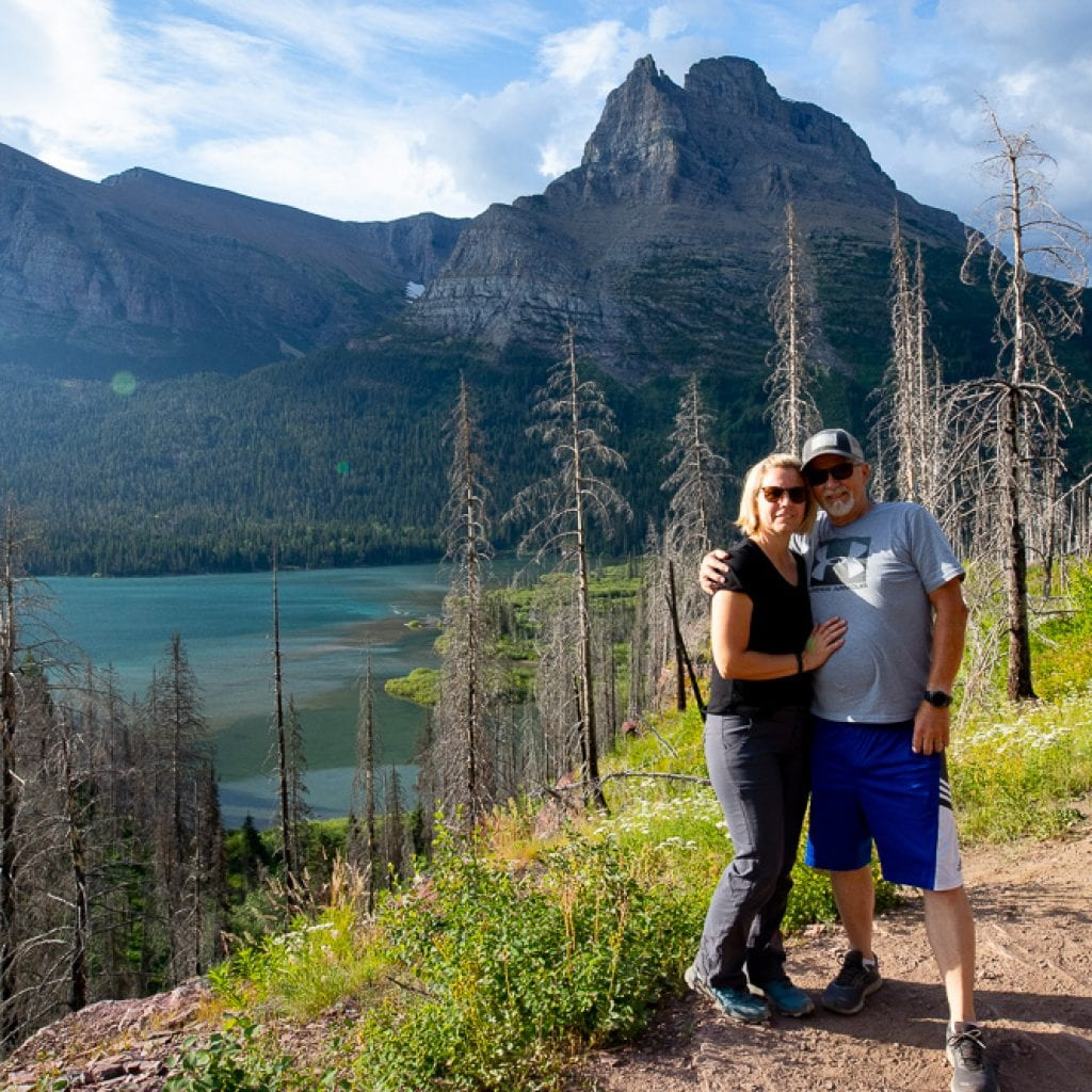 Couple in front of lake on St. Mary's trail Montana