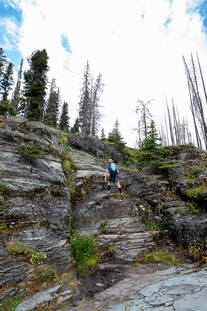 Boy scrambling up rocks at bering falls Montana