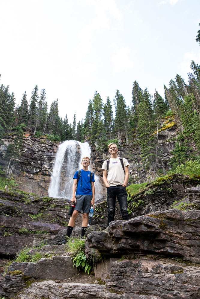 Teenage boys standing in front of Virginia Falls Montana