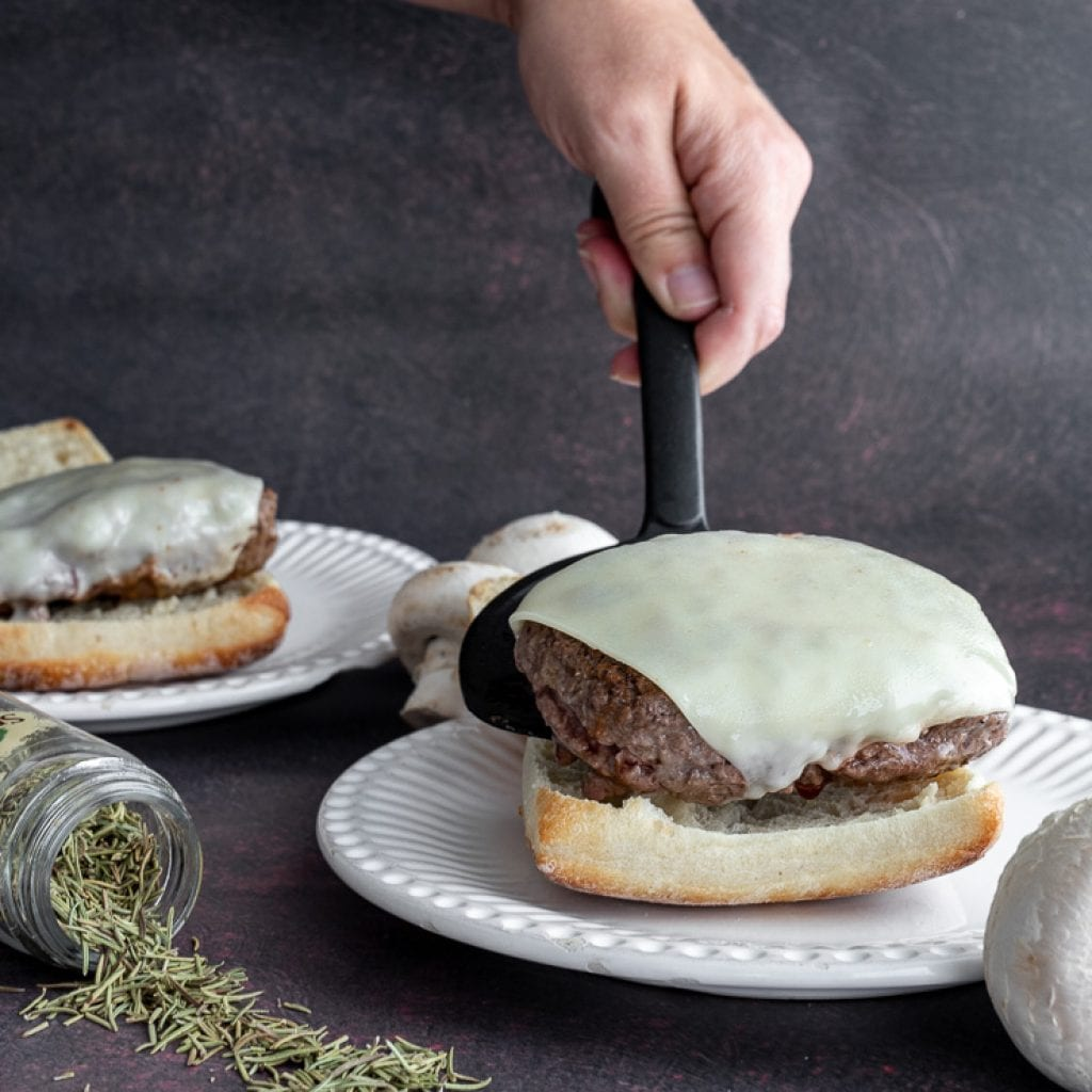 woman add burgers with melted swiss onto artisan bun