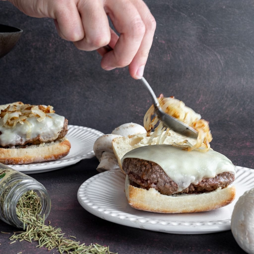 woman adding caramelized onions onto burger with swiss