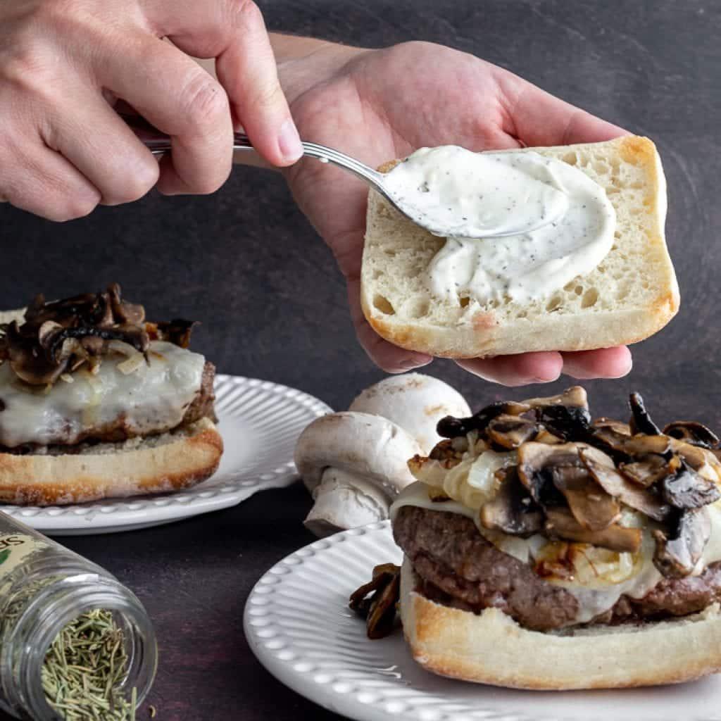 woman spreading aioli onto burger bun