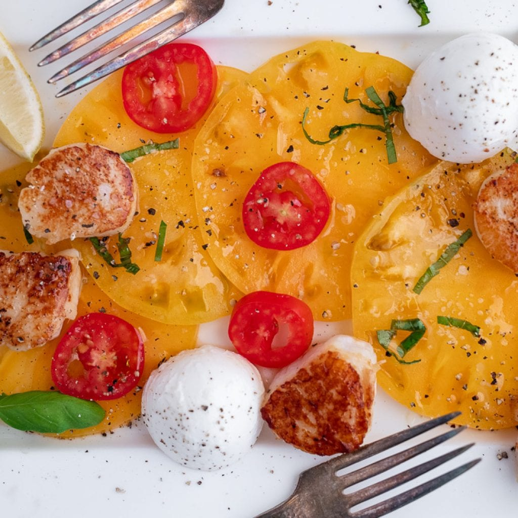 caprese salad with scallops sprinkled with salt and pepper