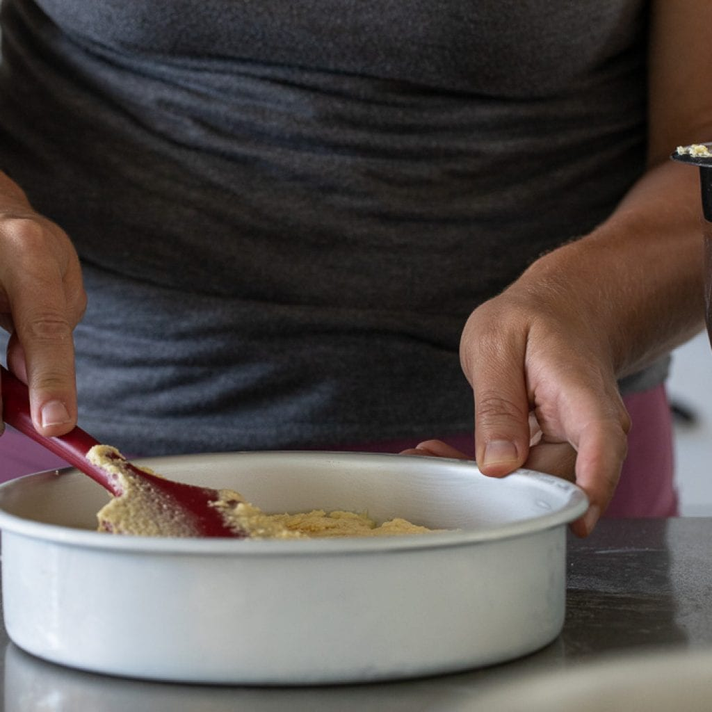 woman spreading cake batter into pan