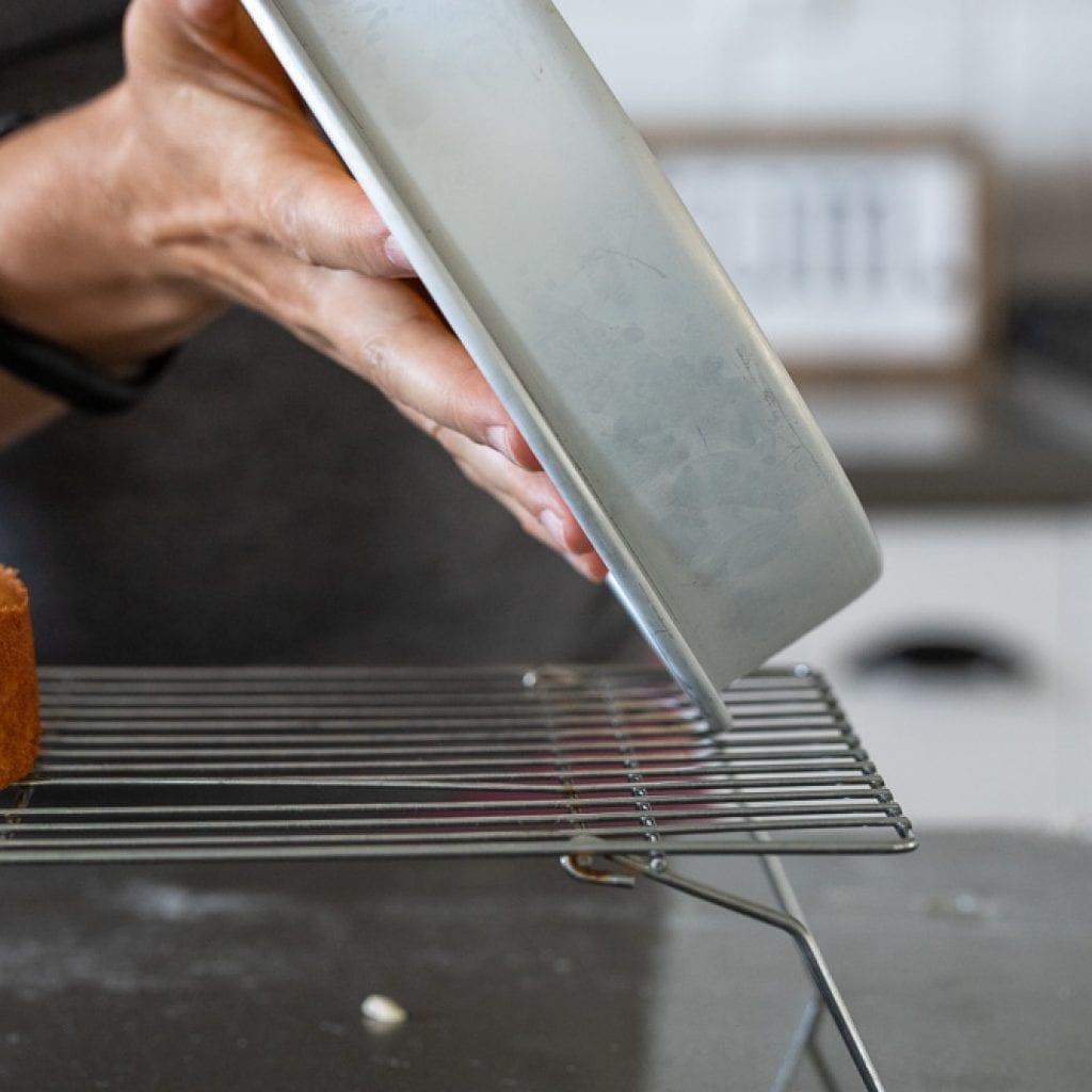 woman removing cake from cake pan
