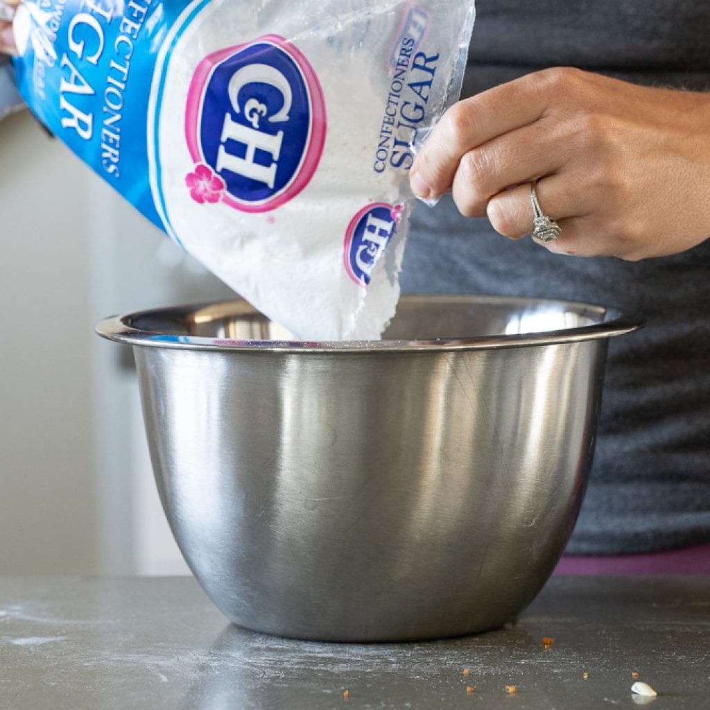 woman adding powdered sugar to bowl