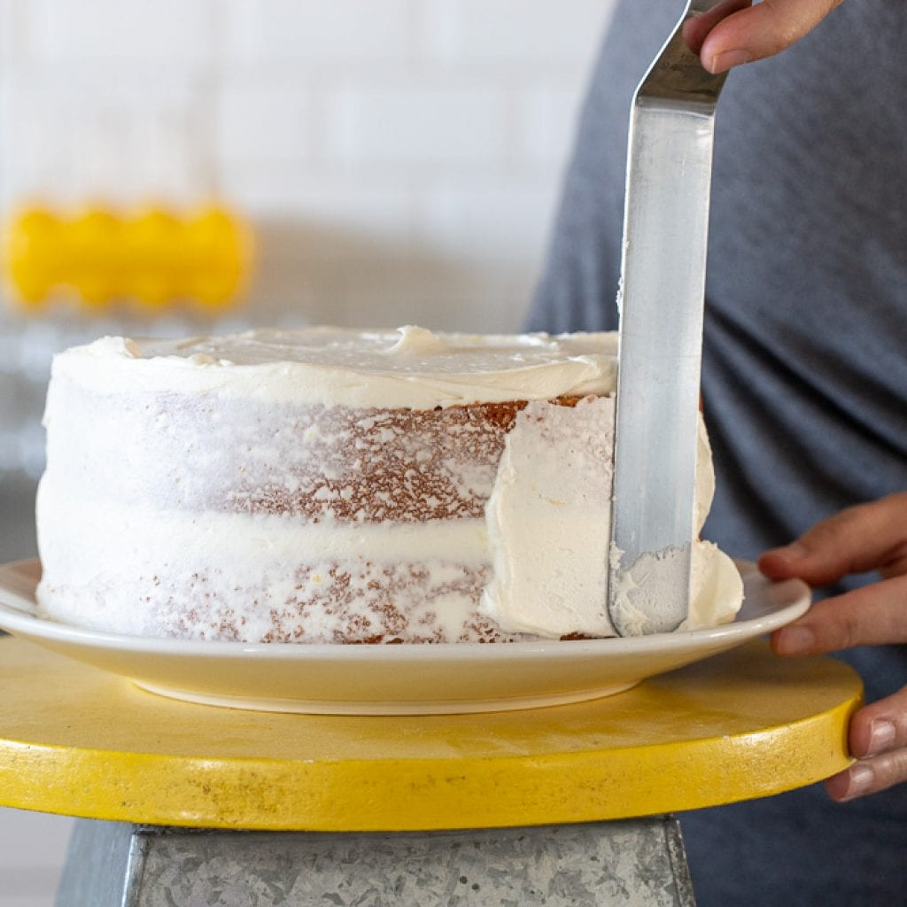 woman icing cake with offset spatula