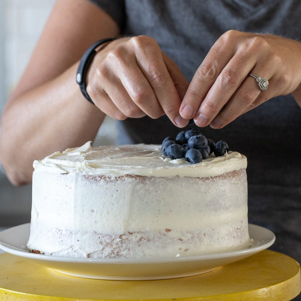 woman adding blueberries to top of cake