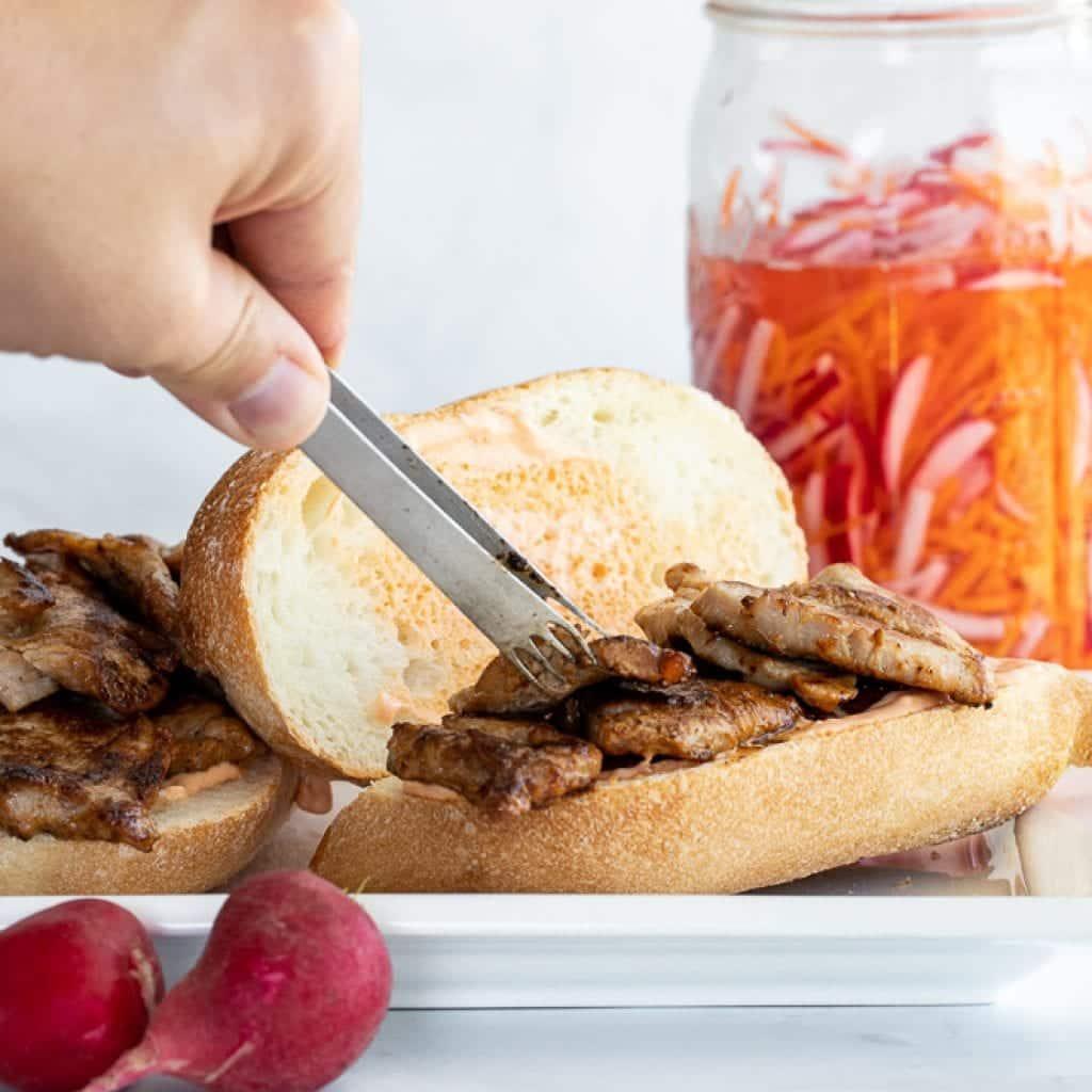 woman adding pork tenderloin to banh mi pork tenderloin sandwiches