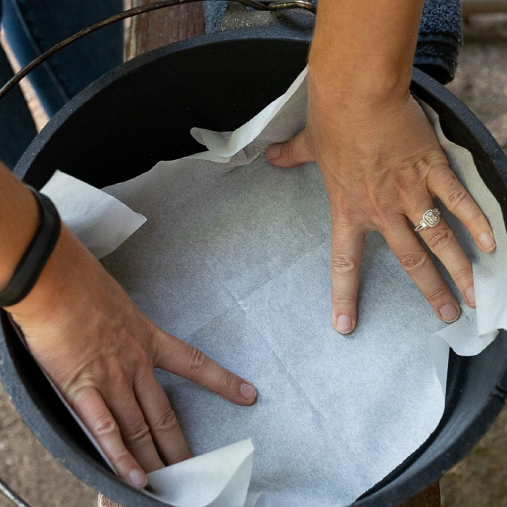 woman placing parchment paper in a dutch oven