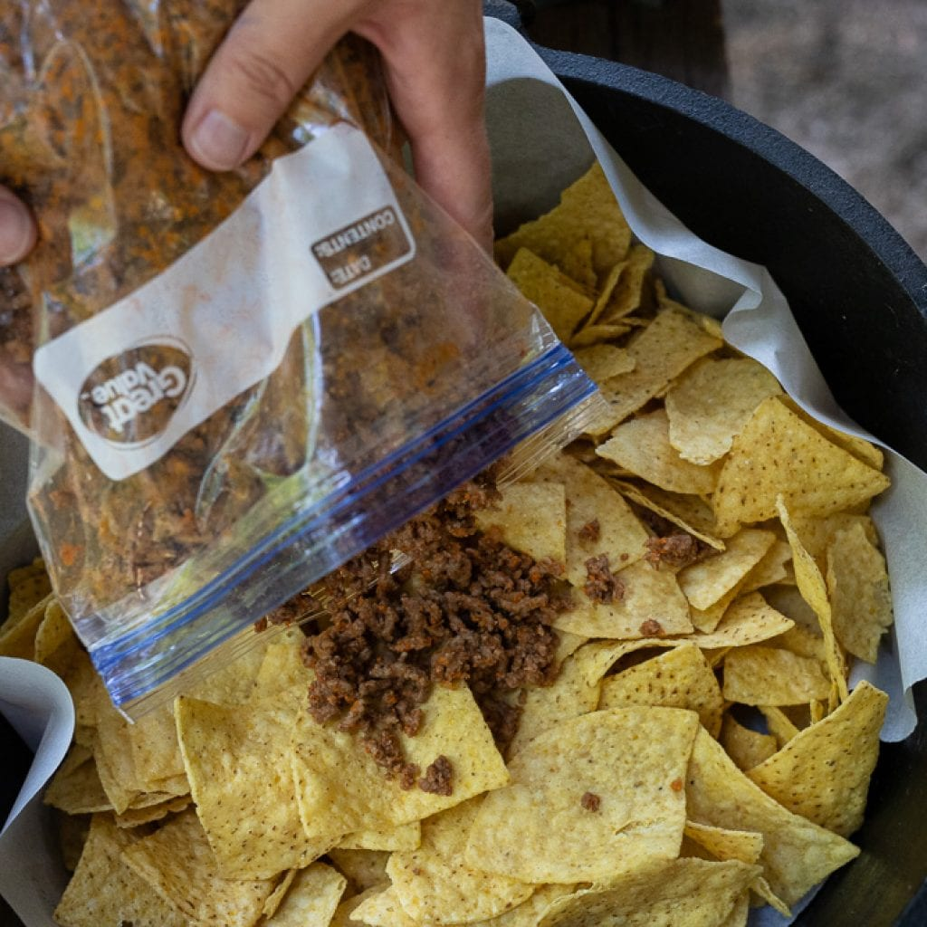 woman pouring mexican style ground beef onto chips in dutch oven.