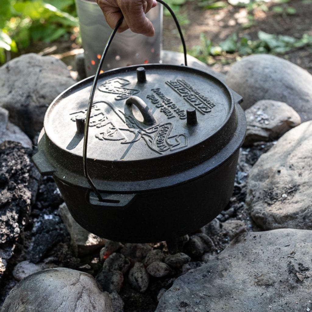 placing dutch oven over coals in fire ring