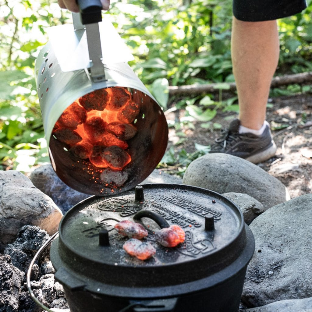 man pouring charcoal over dutch oven for cooking