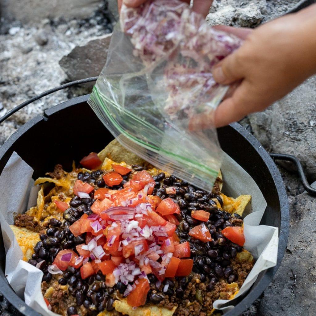 woman adding red onions to nachos