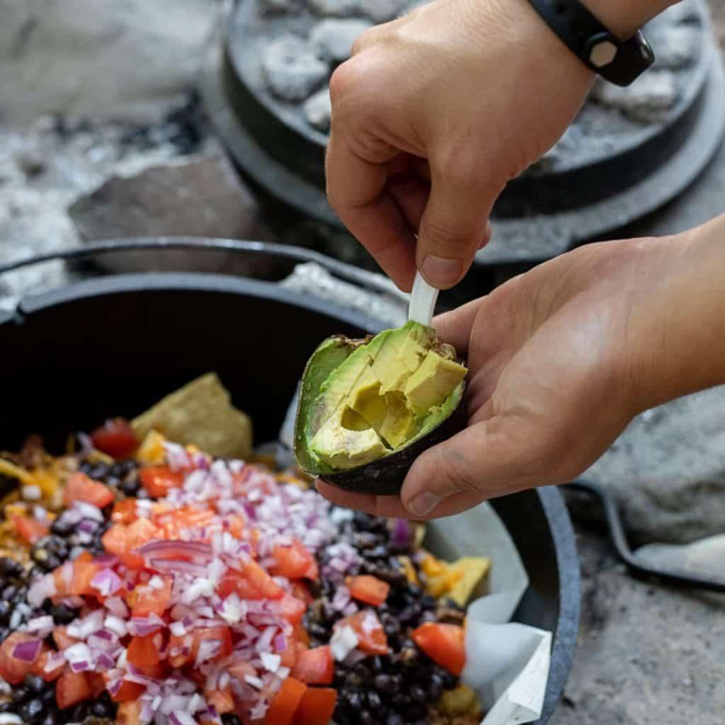 woman adding avocados to nachos in dutch oven