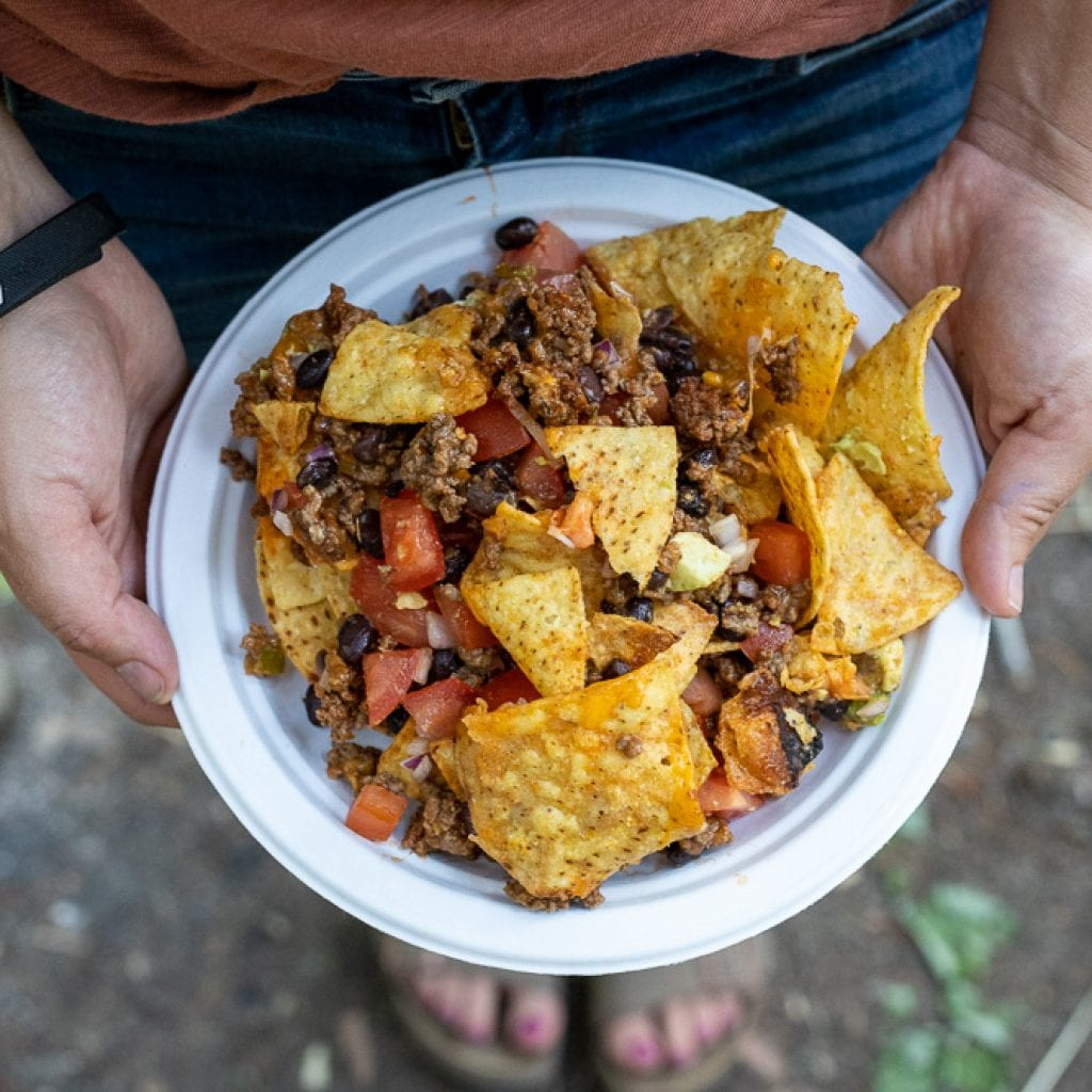 woman holding plate of campfire nachos
