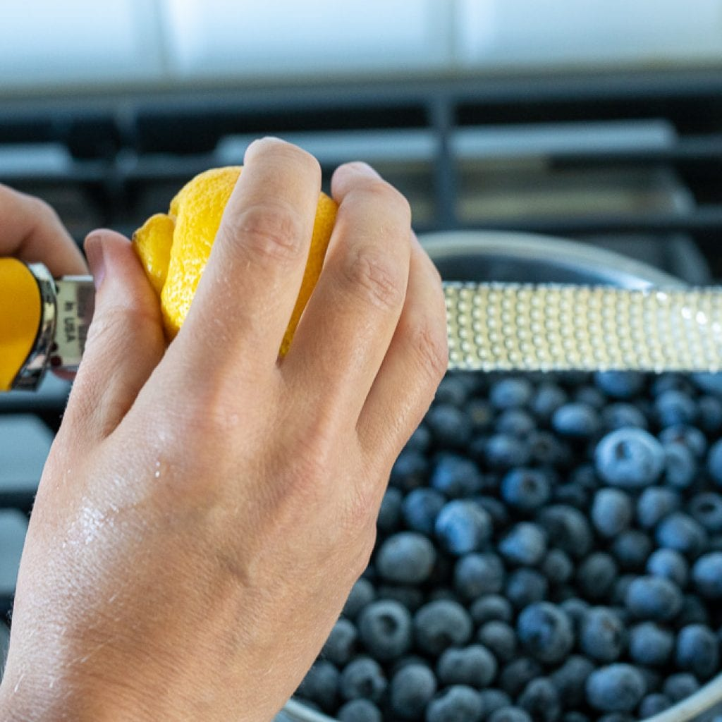 woman zesting a lemon over blueberries in a stainless steel pan