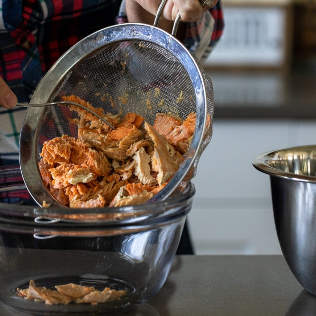 woman pouring salmon from metal mesh strainer into glass bowl