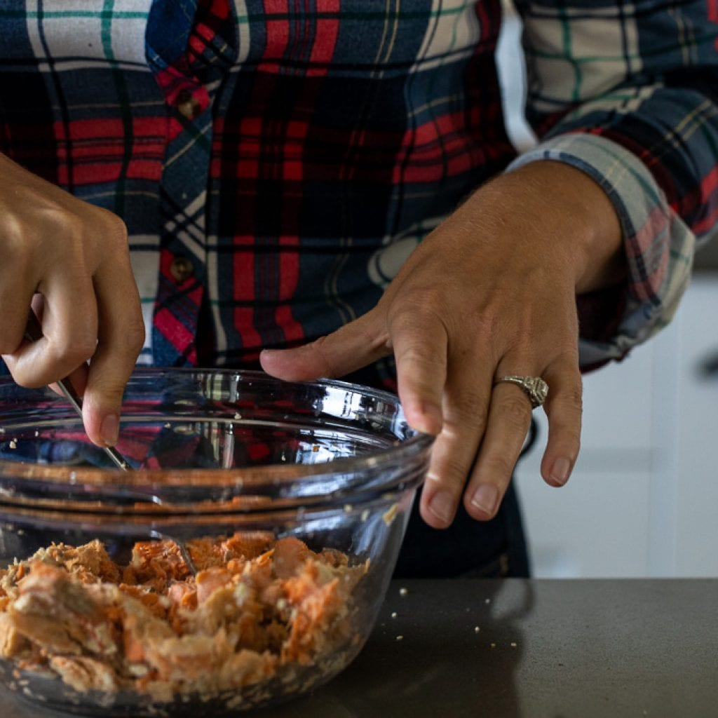 woman flaking salmon in glass bowl with fork