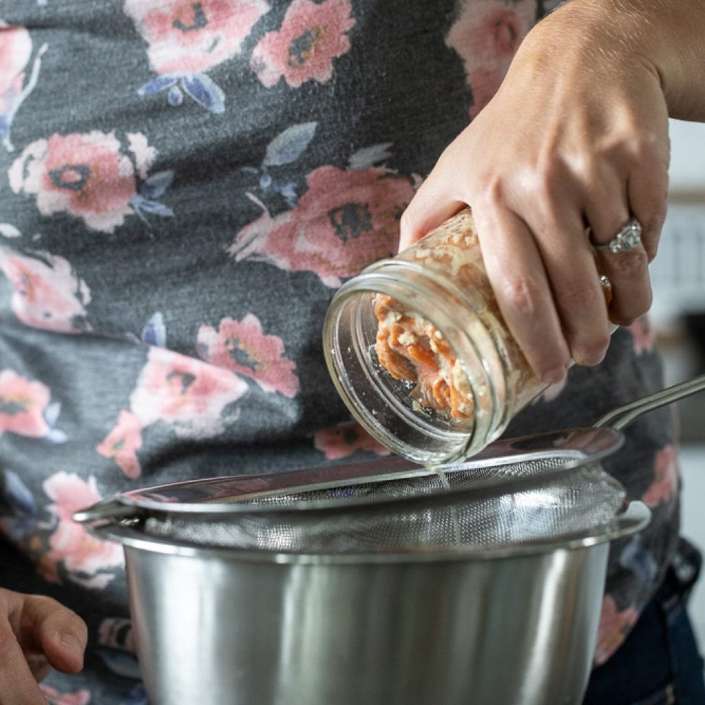 woman pouring canned salmon into strainer over stainless steel bowl