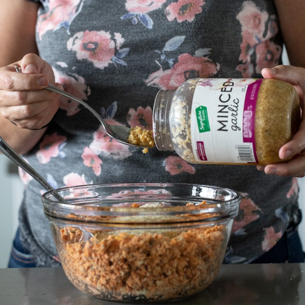 woman adding minced garlic to a clear glass bowl with flaked salmon