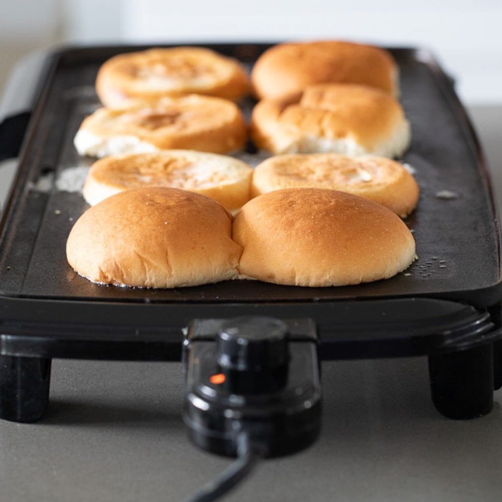 woman cooking hamburger buns on electric griddle