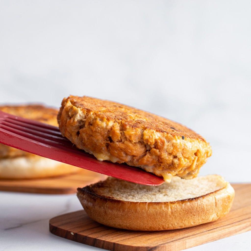 salmon burger being placed on toasted hamburger bun