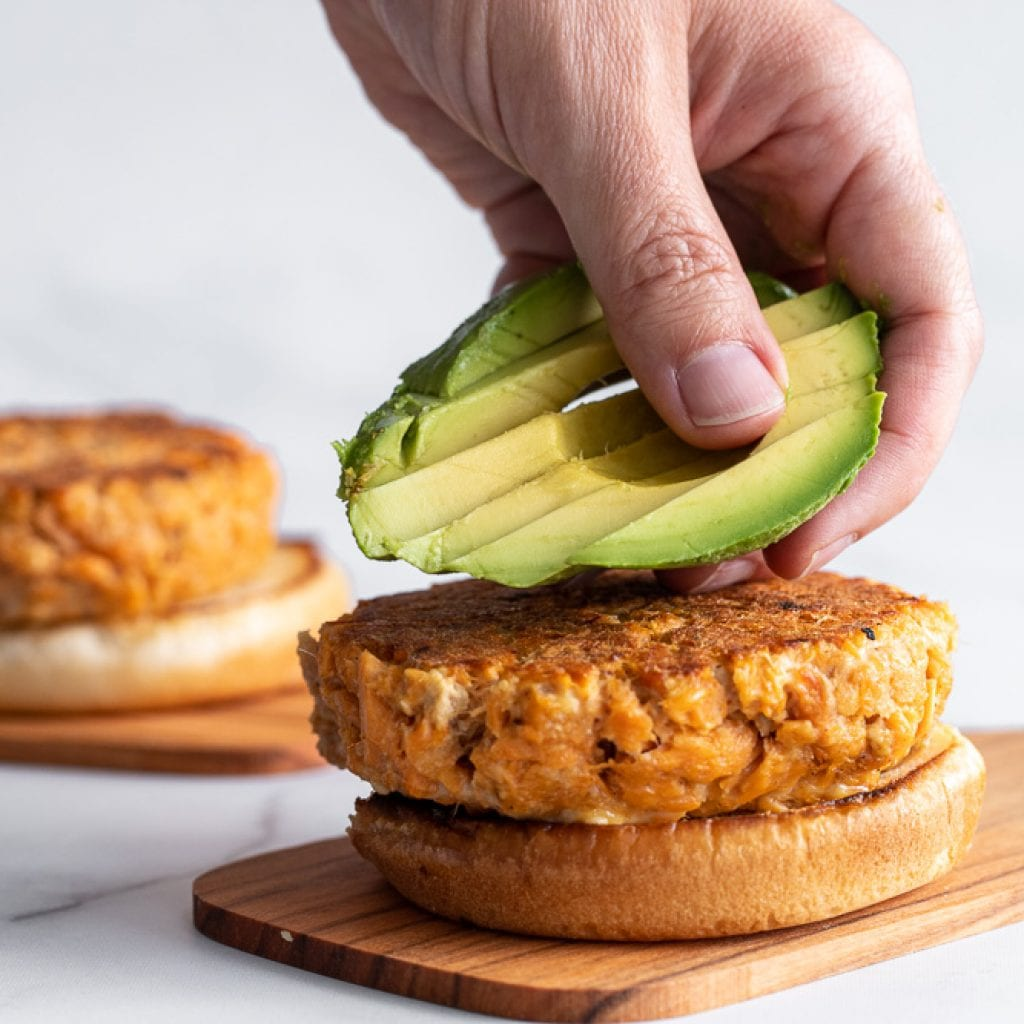 woman placing sliced avocados over salmon burger