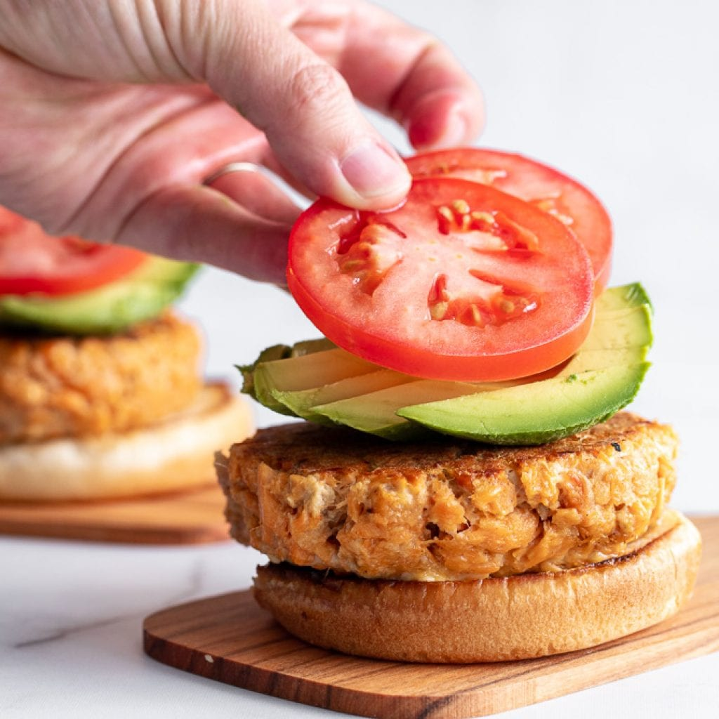 woman layering sliced tomatoes over avocado and salmon burger