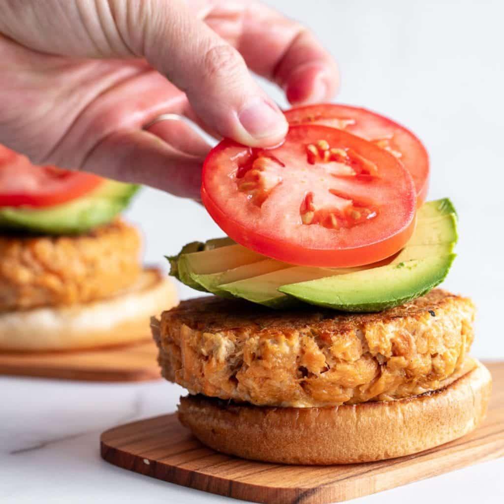 woman layering sliced tomatoes over avocado and salmon burger