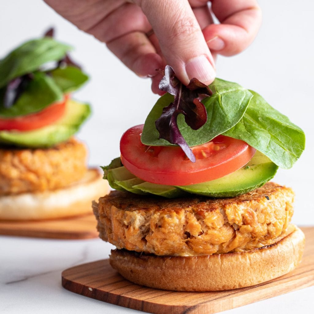 woman adding mixed greens over layered salmon burgers