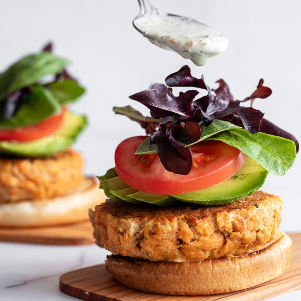 woman drizzling jalapeno ranch over salmon burger