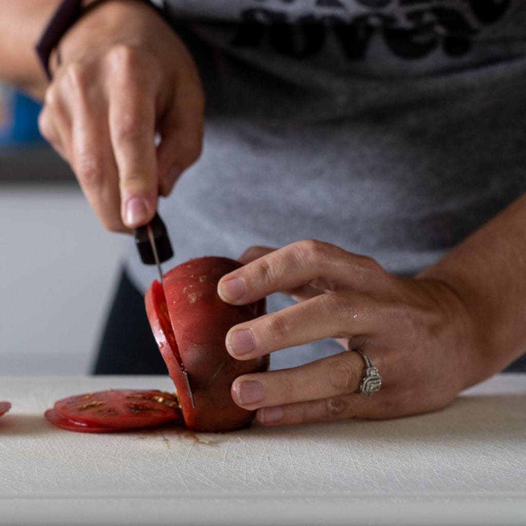 woman slicing a cherokee tomato on a white cutting board