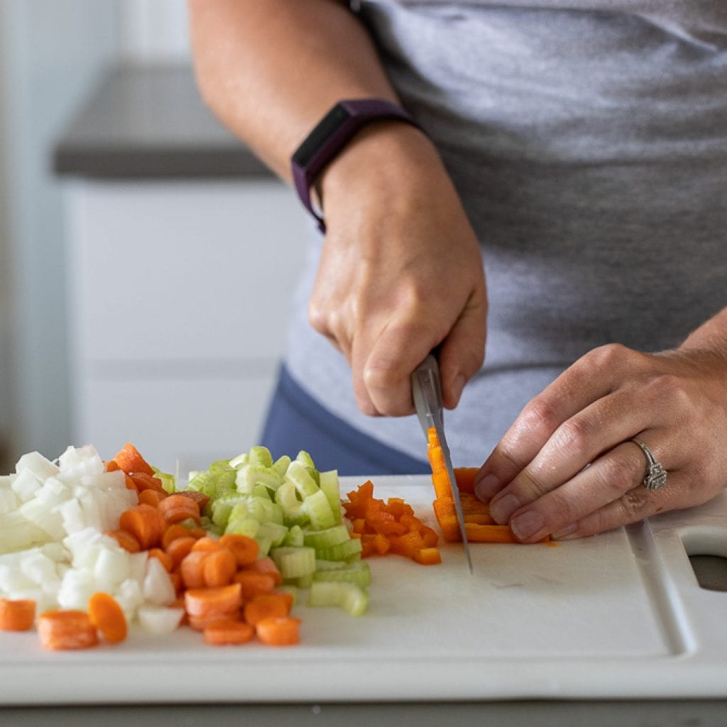 woman cutting bell peppers with chef's knife on plastic cutting board