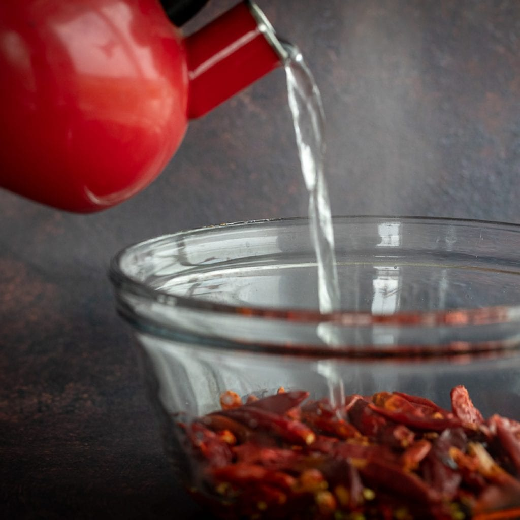 woman pouring boiling water over dried chilies for homemade chili paste