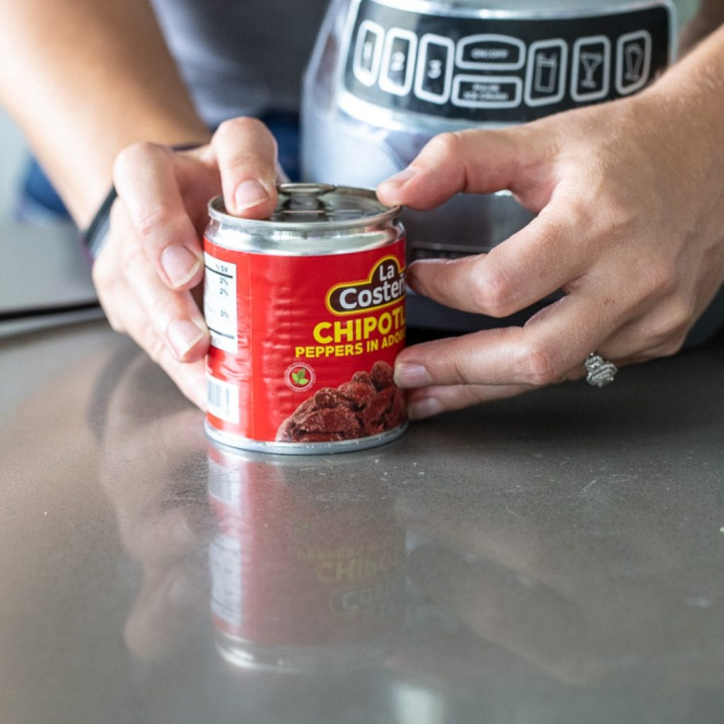 woman holding a can of chipotle chili pepper in adobo sauce for homemade chili paste