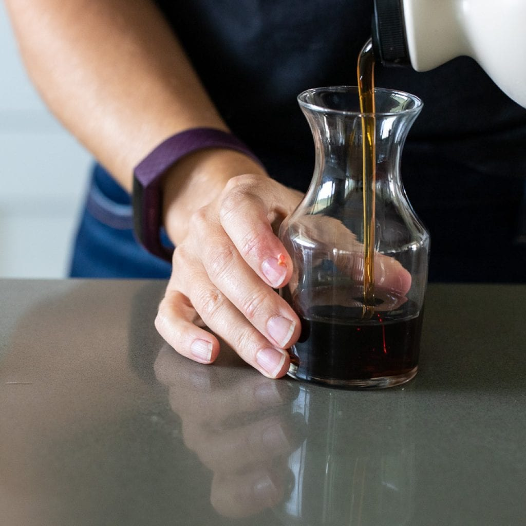 woman pouring maple syrup into glass container