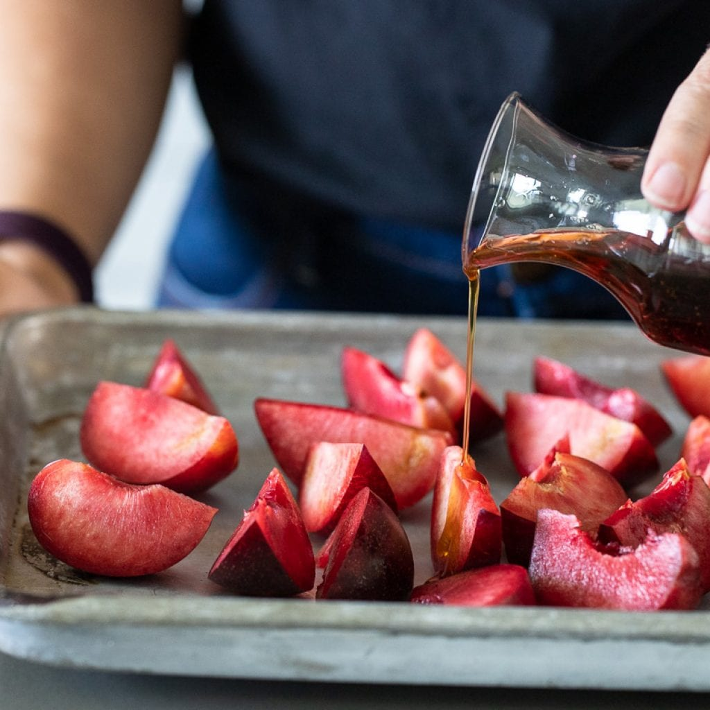 woman pouring maple syrup over plums on a baking sheet for roasting
