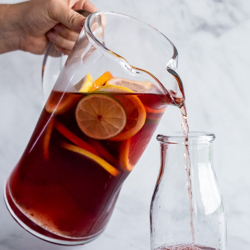 woman pouring the best summertime sangria no alcohol in glass pitcher into a glass milk cup